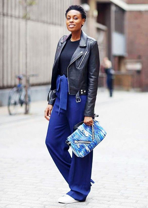 Editor Donna Wallace wears a black t-shirt, leather motorcycle jacket, wide-leg blue trousers, a Kenzo blue bag, and white sneakers