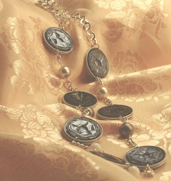Vittoria – Collana con catena argentata a maglie sottili. Cialde nere e carta da zucchero con perline bianche, grigie e latte.