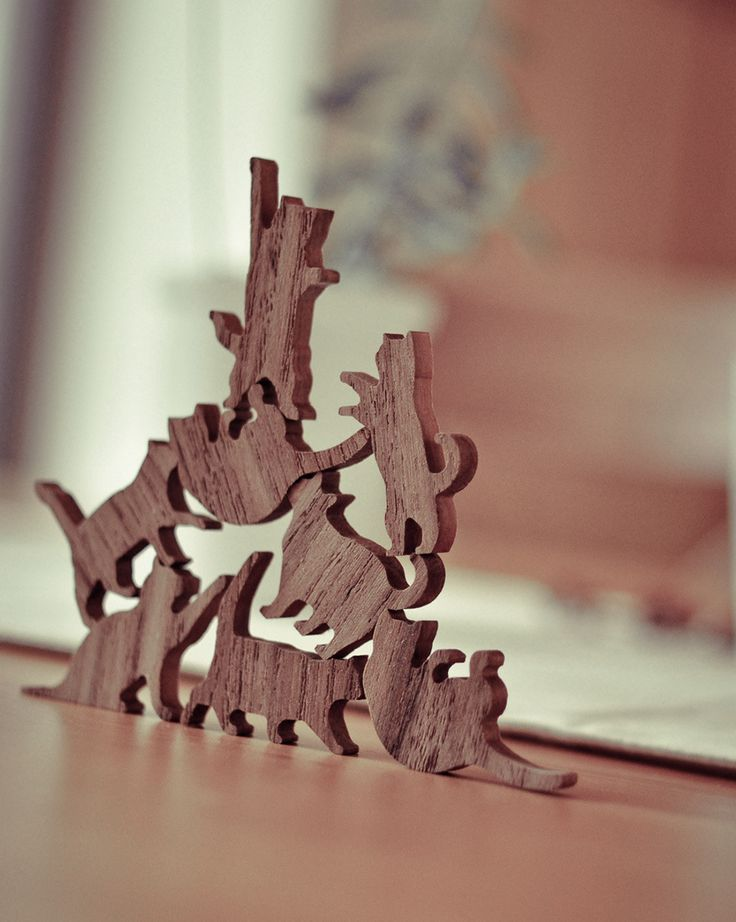 "Wooden Cat Stacking Game. $19.99 - Each set includes six cats in various poses. Laser cut from solid teak, the cats come in 4 different sets including a vast array of cat poses such as the ""stretch & yawn"", ""play time"", ""shrug of indifference,"" and the classic ""feed me or I'll bite your legs."" Cats measure approx. 1"" x 1"""