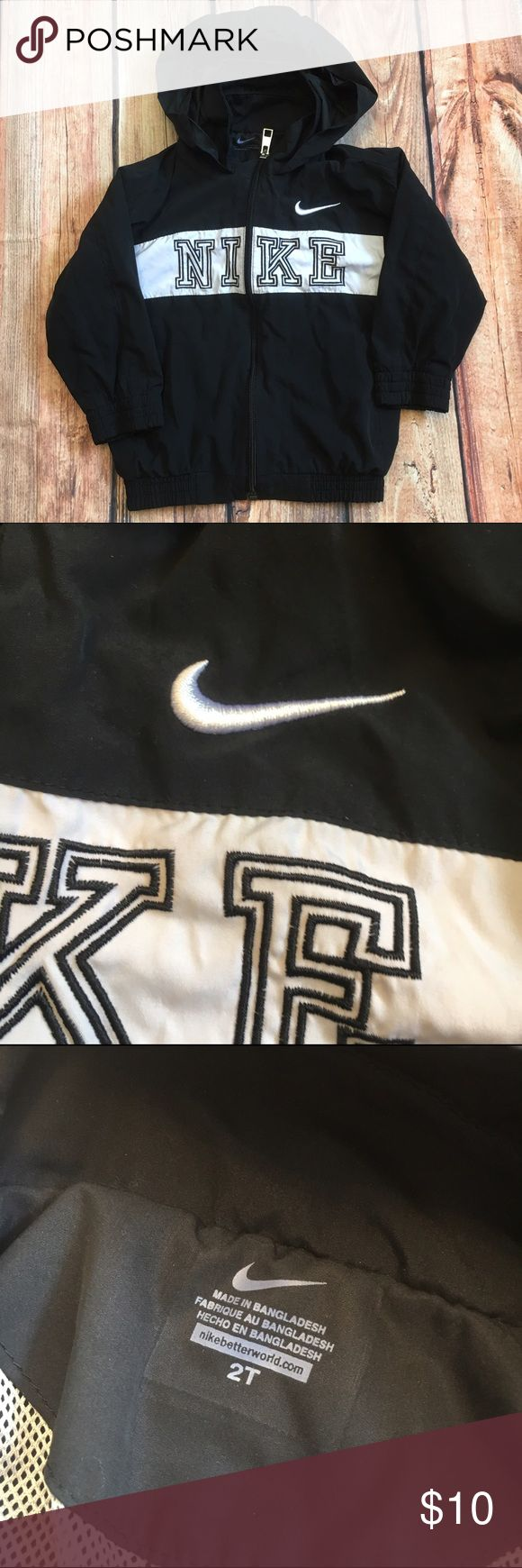 Baby size 2t Nike zip up hoodie black white Size 2t Nike zip up with hood. Hood rolls up and velcros to hide away. Velcro has a few fuzzies. Jacket polyester. In good condition. Nike Jackets & Coats