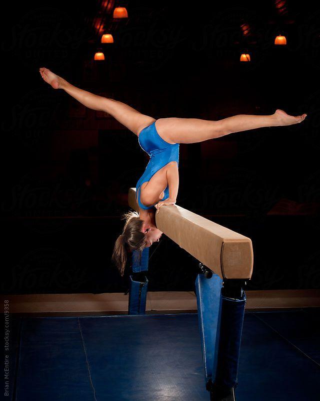 female gymnast in handstand on balance beam routine by brian mcentire