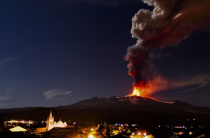 Mt. Etna, spews lava as ash and gases billow during an eruption as seen from Acireale, near the Sicilian town of Catania, on November 16, 2013