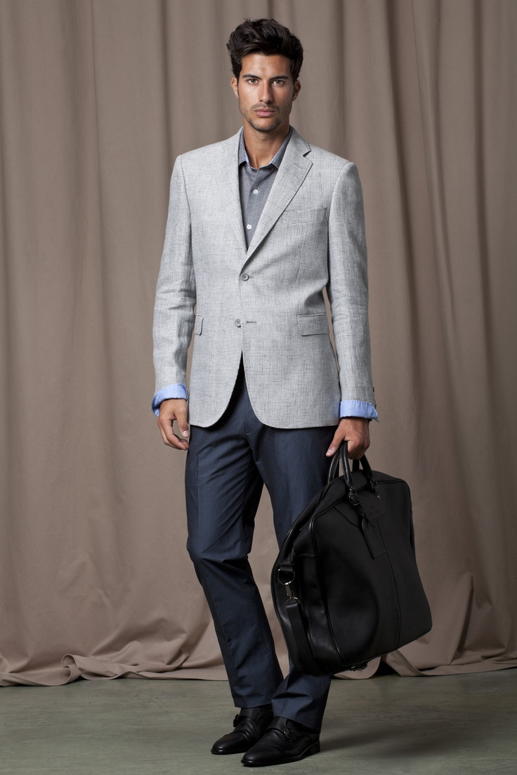 Light grey Blazer, darker grey shirt with light blue cuffs, blue, tailored trousers, black leather shoes and black leather travel bag