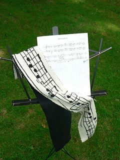 "The musical score for ""Shenandoah"" done in stranded knitting, then backed with a black st st piece.  Wow."