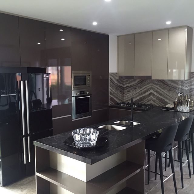 This feature splashback really ties this room together, bringing all the colours of cabinetry and shelving together and creating texture in the kitchen. Just gorgeous, even in a small space. #totalkitchens #marble #stone #kitchen #design
