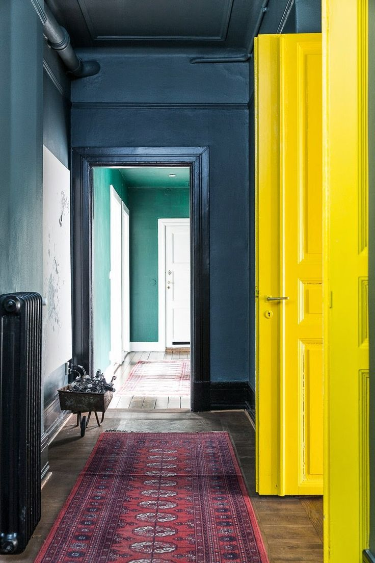 Mixing it up: canary yellow doors, dark wooden floors, teal and blue walls with black frames and radiator. Throw in an eastern rug and somehow it all works