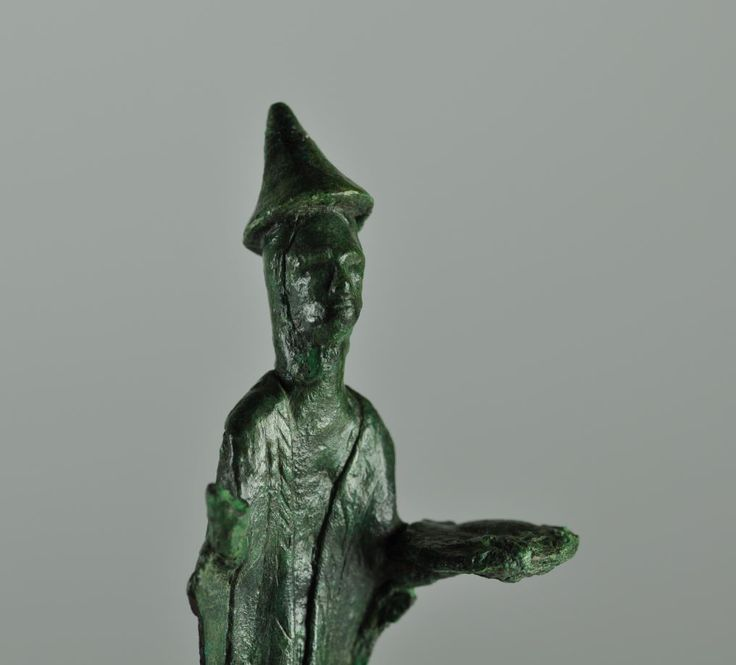 Sardinian bronze priest, 9th-7th century B.C. Sardinian bronze votive figure representing a priest with in the left hand an offering plate,  right hand raised to salute a divinity. wears a hooded long dress, a cape and a stola with engraved decorations, on the head a conical hat, 8.6 cm high. Private collection