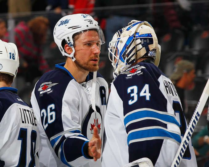 Oct.9 2015 - Wpg 3 - NJ 1 - Winning goaltender Michael Hutchinson #34 of the Winnipeg Jets is congratulated by Blake Wheeler #26 after defeating the New Jersey Devils at the Prudential Center on October 9, 2015 in Newark, New Jersey. The Jets defeated the Devils 3-1. (Photo by Andy Marlin/NHLI via Getty Images)