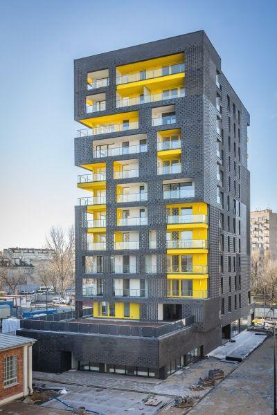 Budynek, który góruje nad całym kompleksem, zaprojektowano tak, aby połączyć w bryle cechy architektury przemysłowej oraz wymogów współczesnego mieszkalnictwa. Dwunastokondygnacyjny gmach wyróżnia się kolorystyką, starannie dobranymi materiałami wykończeniowymi, oryginalnymi podziałami elewacji