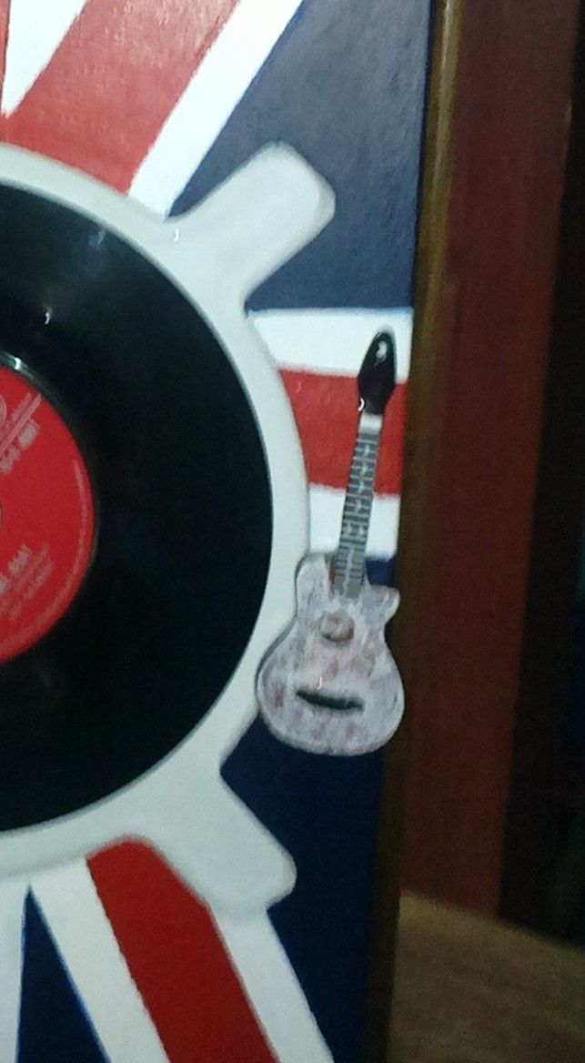 A fridge magnet, of which the magnet previously fell off..! Made a perfect little touch for sticking the guitar onto the front door panel, to use as a door handle.!