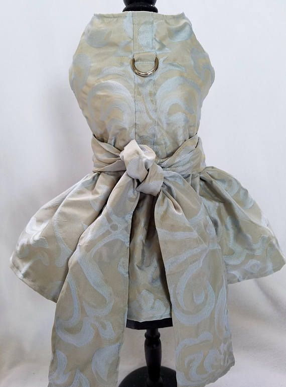 Absolutely beautiful designer dog dress in a shimmery seafoam damask pattern with a golden beige contrast. Perfect for season or occasion. Available in XXS - M.  Garment is fully lined.  Adorable bow tie doubles as front velcro closure.  Extra long ties wrap around your dogs and tied