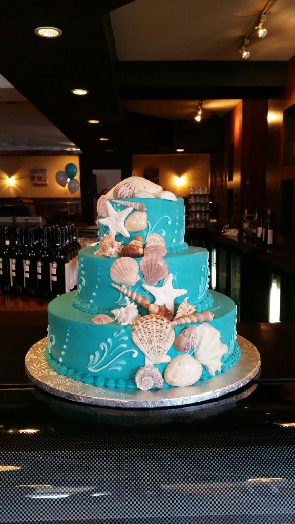 Under the sea themed wedding cake with sea shells.