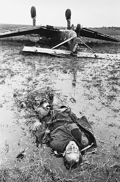 A Ju-87 Stuka bomber lies upside down in a marsh in the vicinity of Leningrad. The inverted gull wings and fixed spatted undercarriage are clearly visible. One of the two-man crew lies in the foreground. This was an attempt at forced landing which didn't work because of the marshy ground. Sept 1943.
