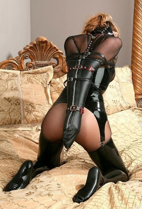 Girl struggling in leather bondage harness