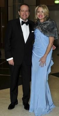 Canberra goes Gatsby for the Midwinter Ball at Parliament House. Bill Shorten and Chloe Bryce arrive at Parliament House for the Midwinter Ball.  Chloe wearing Powder Blue Natalie gown and faux fur caplet. Designer Lucy Laurita of Leiela. Full article http://www.smh.com.au/lifestyle/fashion/canberra-goes-gatsby-for-the-midwinter-ball-at-parliament-house-20140618-zsdws.html