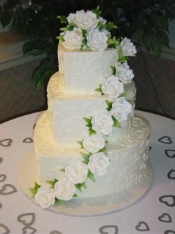 Heart shaped wedding cake with white scrolls and cascading flowers
