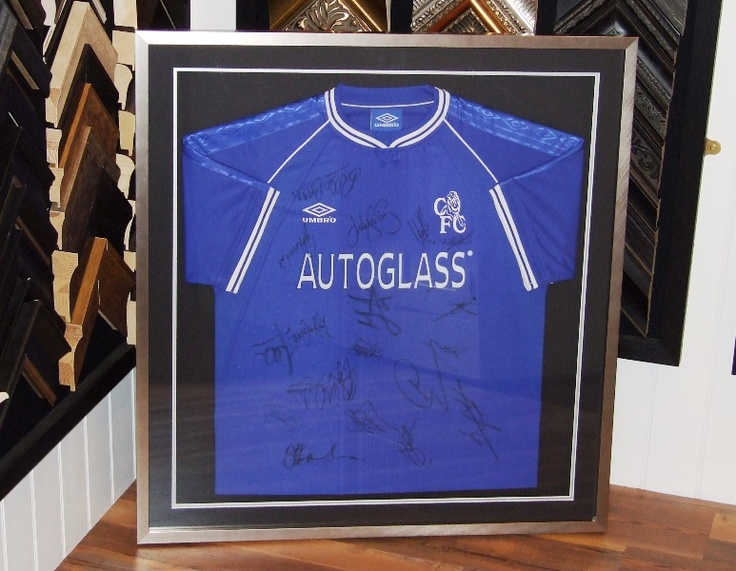 Football shirt with sleeves visible to the front, framed in contrasting black and silver.