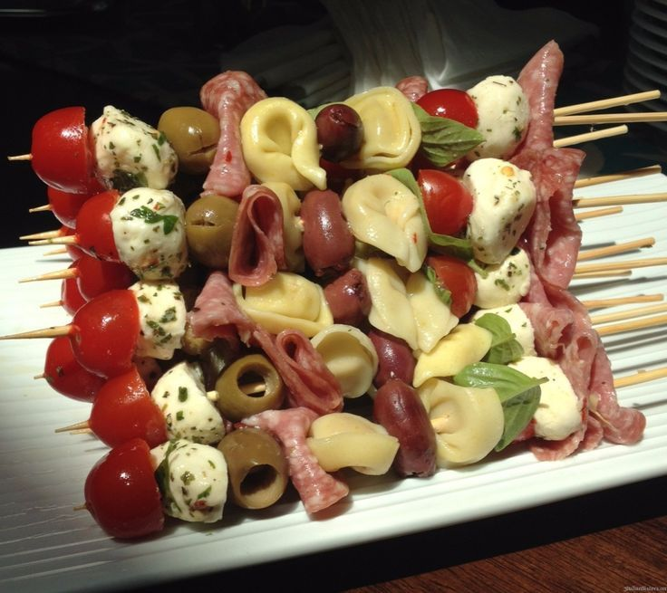 Easy Antipasto Skewers-cheese tortellini pasta, grape tomatoes, Genoa salami (folded in thirds), fresh basil leaves, marinated mini mozzarella balls, green Sicilian olives and black Calamata olives.   Make sure you follow the same pattern when skewering .. They will look more uniform and prettier when piled on top of each other.  Use a smaller 9″ wooden skewer vs a 12″ wooden skewer.