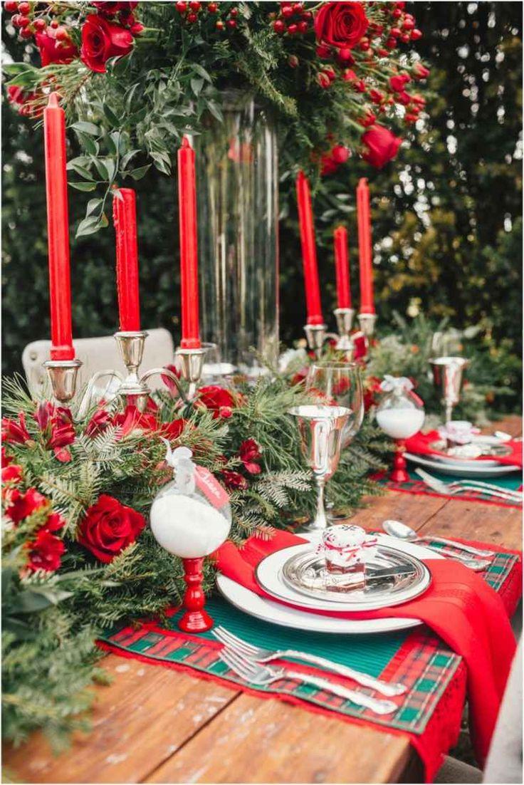 Ένα χριστουγεννιάτικο τραπέζι σε πράσινο και κόκκινο με μια ρύθμιση λουλουδιών από έλατο υποκαταστήματα