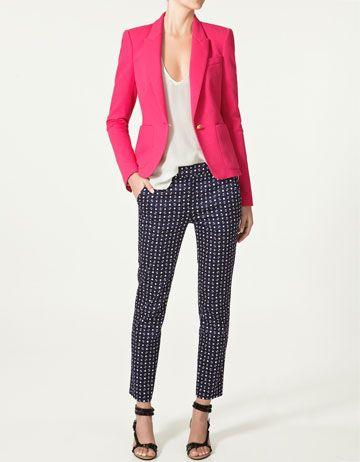 Calça azul, blusa clara, paletó vermelho