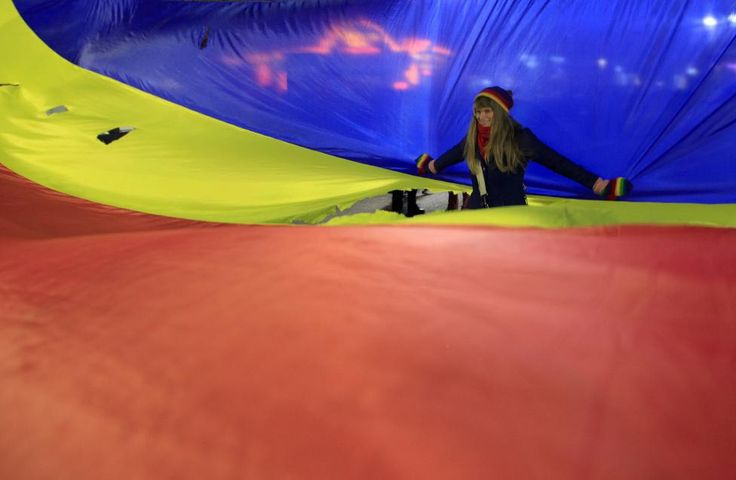 A woman poses inside a hole in a large Romanian flag during the 25th anniversary of the country's 1989 revolution in central Bucharest December 21, 2014. REUTERS/Radu Sigheti