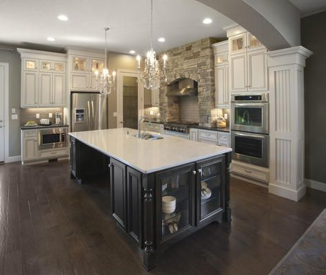 I love that the island cabinets are a darker color than the other cabinets and the dual chandeliers over the island look amazing in this gorgeous kitchen