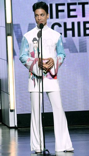 2010 Prince accepts a BET Award Lifetime Achievement Award, wearing a shirt with a drawing on his chest and sky blue sleeves at The Shrine Auditorium on June 27, 2010 in Los Angeles. | Billboard