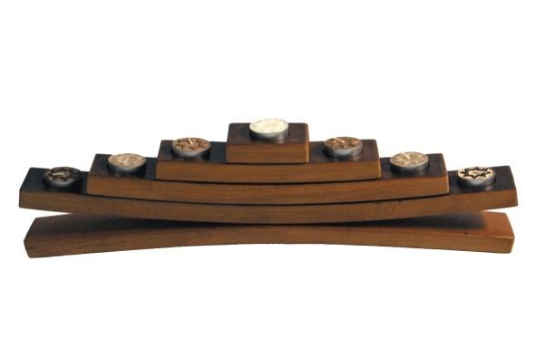 Elegante candelabro de madera con forma piramidal, lijado y barnizado, con capacidad para 7 velas, su particular forma curvada, propia de las duelas de la barrica de la que proviene le convierten en un portavelas con encanto y originalidad, lejos de de los típicos materiales plásticos y formas rectas que suelen acompañar a este tipo de accesorios.