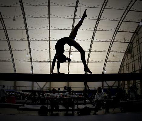 gymnast on balance beam, women's gymnastics, silhouette, cool sports photography action photo,