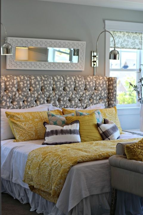 rectangular mirror with clean sconces on either side of the bed