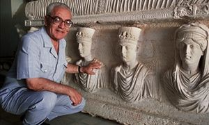 A 2002 picture of Khaled Asaad in front of a rare sarcophagus from Palmyra depicting two priests dating from the 1st century.