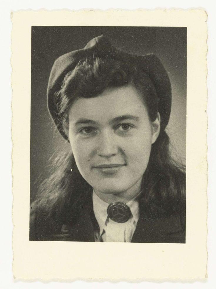 Fotodienst NSB | Portret van een jonge vrouw, lid NSB, Fotodienst NSB, 1940 - 1944 | Portret van een jonge vrouw, lid NSB. Zij draagt een soort alpinopet en een speld met een runeteken: het wentelend zonnerad. Zij heeft lang, donker haar.