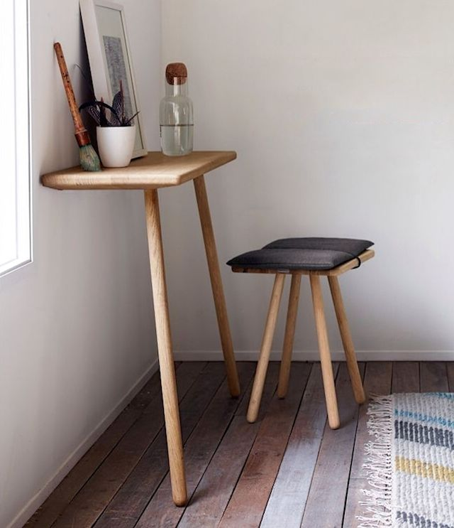 Minimalist desk and stool, natural wood with rounded corners.
