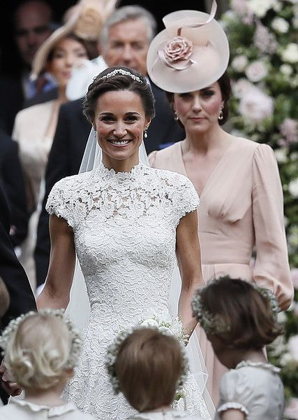 Kate Middleton Photos Photos - Britain's Catherine, Duchess of Cambridge, (R) follows her sister Pippa Middleton following the wedding of Middleton to James Matthews at St Mark's Church in Englefield, west of London, on May 20, 2017..After turning heads at her sister Kate's wedding to Prince William, Pippa Middleton graduated from bridesmaid to bride on Saturday at a star-studded wedding in an English country church. Middleton married financier James Matthews, 41, at a ceremony attended by…