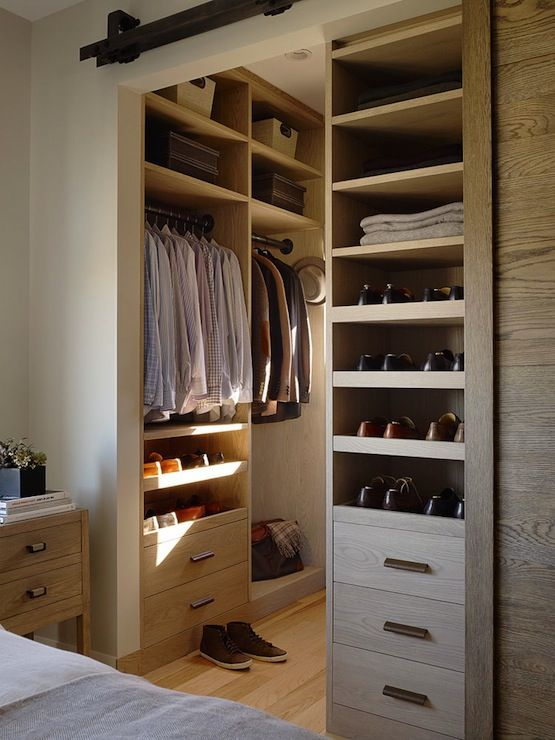 Masculine closet design with interior sliding barn door opening to built-in shoe shelves, built-in drawers, built-in clothes storage and woven baskets.