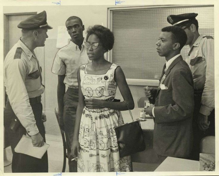 """July 21, 1961-- Unidentified HPD officer with two """"Freedom Riders,"""" Frank Johnson, 21, left, and Pat Baskerville, 18, both of Tucson, Ariz., and Eldrewey Stearnes, right, head of the Progressive Youth Association, in custody at the Houston police station. The freedom riders and Stearnes were arrested by HPD at the Union Station coffee shop in Houston to end a sit-in demonstration. Dan Hardy, HP Staff."""