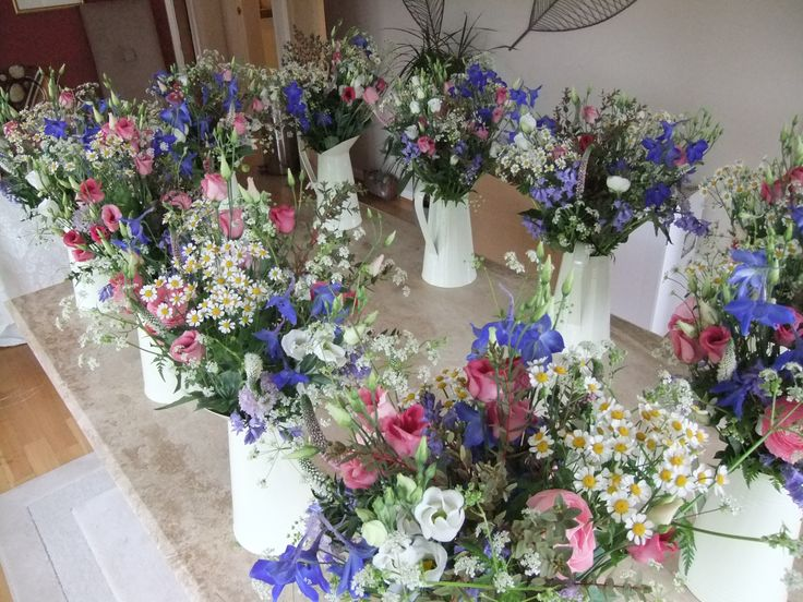 Ten table jugs of spring flowers awaiting delivery