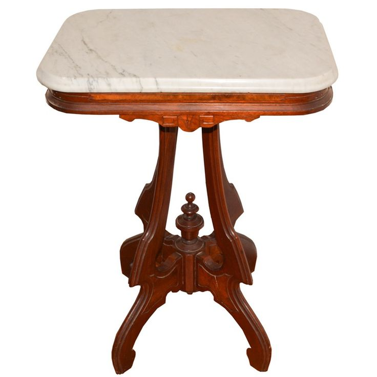 A marble top side table. This early 20th Century table features a removable white marble top set upon a pedestal base with cabriole legs and scroll feet. The table is unmarked.