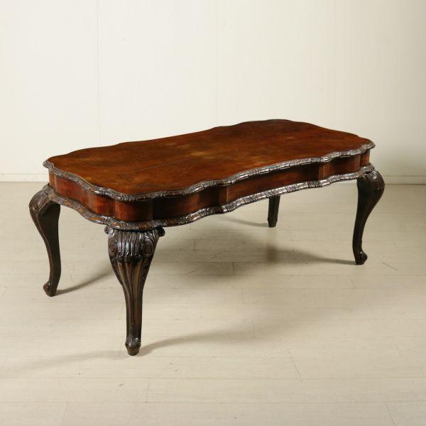 Tavolino in stile barocchetto retto da grandi gambe mosse e intagliate. Presenta fascia sagomata con cornici. Piano impiallacciato piuma di noce.
