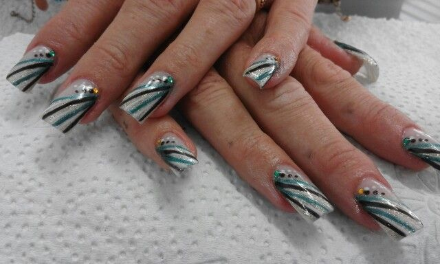 Slanted gold french with free hand drawn emerald green stripes, black stripes and white stripes.  White & black dots finished off with green and gold diamontes
