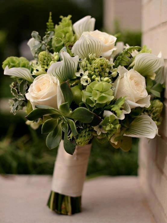 Huge creamy roses, star-of-bethlehem, lady's slipper orchids, succulents, foliage and fern. A mesmerizing bouquet!