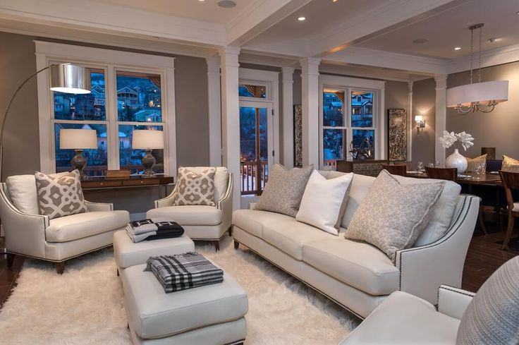 Lush white shag rug over dark hardwood flooring supports this white leather furniture set, including twin rectangle ottomans with cushion tops.