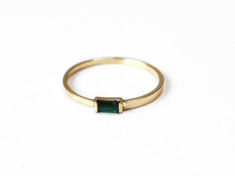 A beautiful little gem that makes a big statement! A baguette shaped emerald sits in 14K yellow gold. A modern simple piece to add to your stack!