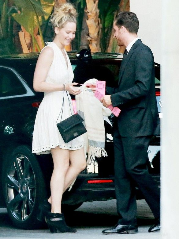 Jennifer Lawrence wears a little white dress, black bag, and black booties