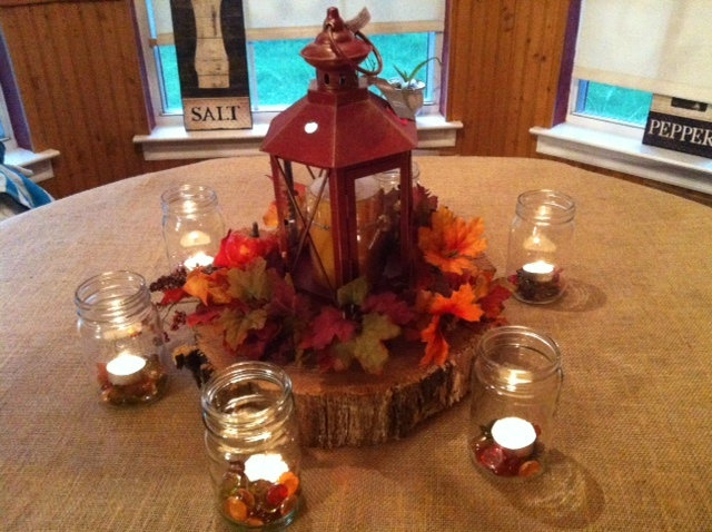 Playing around with fall centerpieces: Burlap table cloth, Fall leaves, Lantern, Mason Jars, Wood Slab, Fall Colored jewels from Pier One, Tea lights - Add some jute ribbon and raffia around the mason jars and it would be rather pretty!