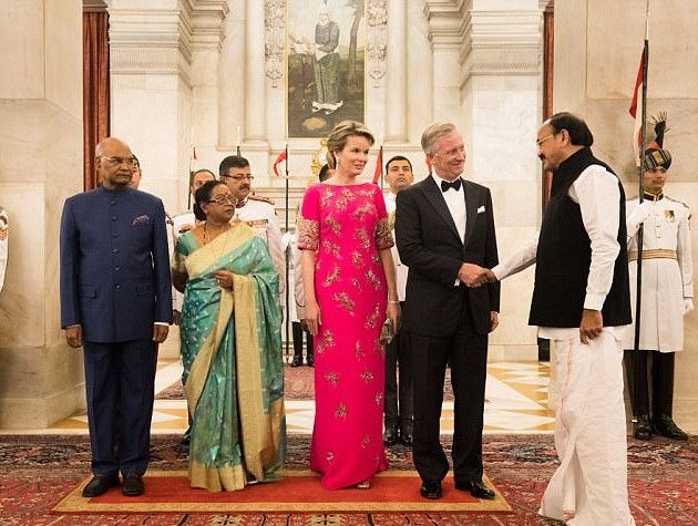 (L-R) Indian President Ram Nath Kovind, his wife Indian First Lady Savita Kovind who was dressed in a traditional gold and green sari, Queen Mathilde wears an Indian inspired dress and King Philippe of Belgium as they meet officials at the Presidential palace for a lavish banquet.