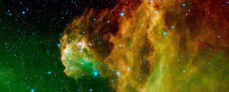 """Regione chiamata Barnard 30, punteggiata di giovani stelle (i """"puntini"""" rosa nella foto) formatesi grazie alle onde d'urto di un'antica supernova. Gli sprazzi di verde indicano la presenza di idrocarburi policiclici aromatici, molecole organiche che si trovano anche sulla Terra nei gas di scarico delle automobili. In arancione brillano le particelle di polveri stellari riscaldate dagli astri nascenti, in blu le stelle della Via Lattea sullo sfondo."""