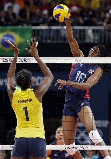 USA's Foluke Akinradewo (16) goes high in the air to spike over Brazil's Fabiana Claudino (1)