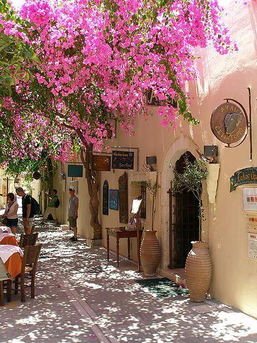 A street scene with the bouganvillea vines in bloom, Rethymno, Crete.