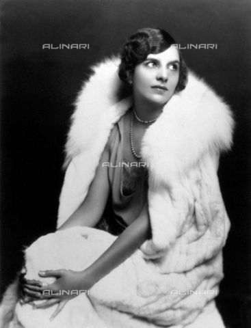 Portrait of a young woman seated with her hands around her knees. She wears an elegant evening gown and fur, 1920s style (c)Monroe, Edward Thayer Fratelli Alinari Museum Collections-Palazzoli Collection, Florence